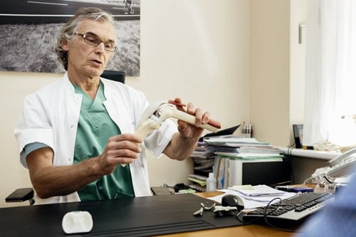 Uitleg van dokter met plastieke voorstelling van knie