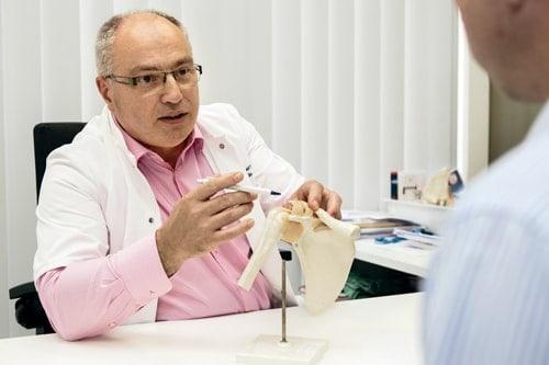 Uitleg van dokter met plastieke voorstelling van schouder